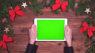 Hands holding digital tablet with green screen on Christmas background