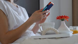 Hands of woman using telephone in bed