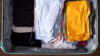 Hands packing suitcase for summer vacation