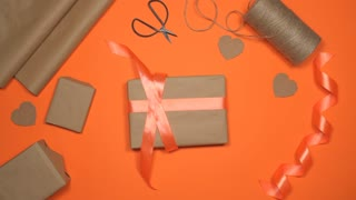 Hands wrapping gift box on pink flat lay