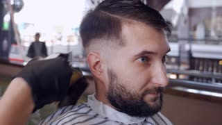 Handsome man getting his head shaved by barber