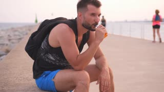 Handsome man sitting by the water and vaping cigarette