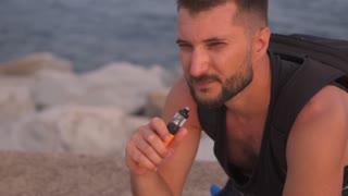 Handsome pensive bearded man vaping cigarette at beach