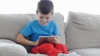 Happy boy on sofa playing with digital tablet