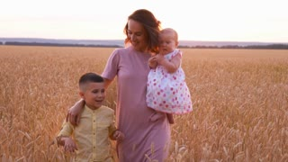 Happy Caucasian family walking in wheat field at sunset