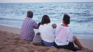 Happy family relaxing by sea