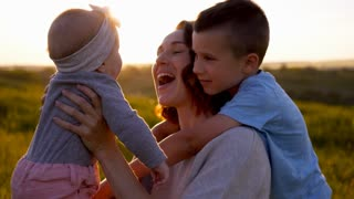 Happy family spending time together in field at sunset