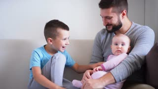 Happy father and son playing with cute daughter