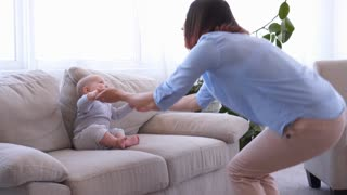 Happy mother dancing with little baby on sofa