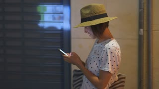 Happy woman texting on phone while strolling outside in city