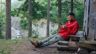 Happy young hiker messaging on mobile phone