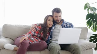 Husband embracing wife while sitting together with laptop on sofa