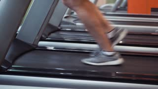Legs of athlete running on treadmill at the gym