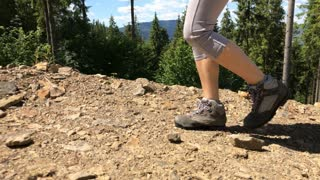 Legs of female hiking in boots and short leggings in mountains