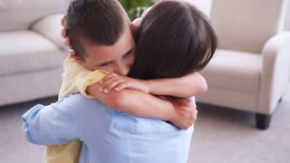 Lovely boy hugging and kissing his mother