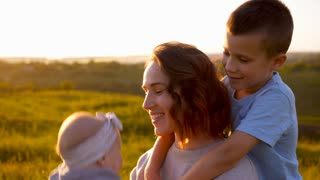 Loving mother having fun with kids in field