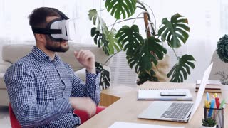 Male in virtual reality goggles orienting in space sitting at table