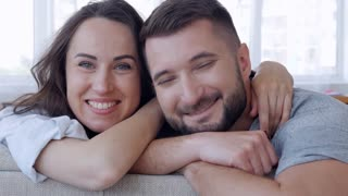 Man and woman in love with each other leaning on sofa