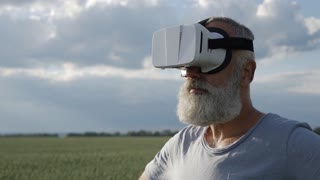 Man in VR glasses moving objects while standing in green field