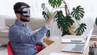 Man in VR glasses orienting in space sitting at table