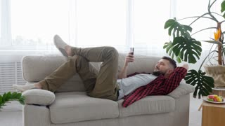 Man lounging on the sofa while having telephone conversation