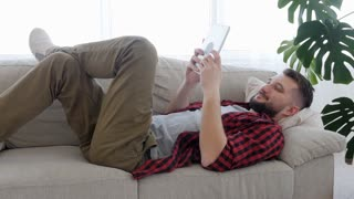 Man lying on the sofa and playing on the tablet