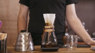 Man preparing pour over coffee at cafe counter