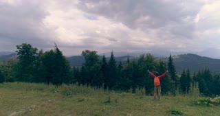 Man standing on edge at mountain peak while raising hands