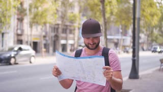 Man tourist planning route with map and mobile phone
