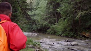 Man traveler with backpack hiking along mountain river