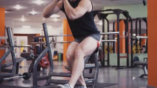 Man with perfectly trained body doing squats on fitness ball