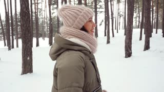 Merry person having fun while strolling in the woods on winter day