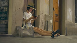 Modern Caucasian woman sitting on stairs and texting in street