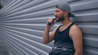 Modern man with beard smoking electronic sigarette outdoors