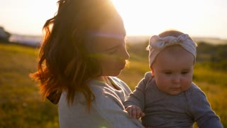 Mom hugging little daughter in sunset lights in field