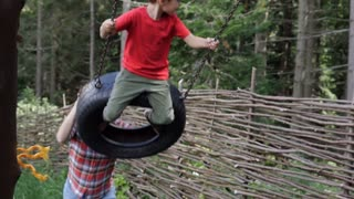 Mom swinging happy boy on tire swing, slow motion
