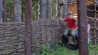 Mom swinging son in swing