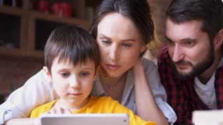 mother and father watchin small son playing games on digital tablet