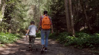 Mother and son holding hands on hiking trail