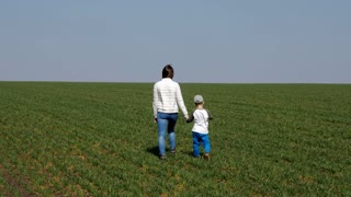 Mother holding hand of son and walking in field