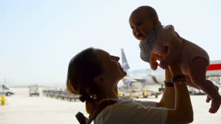 Mother lifting baby above head in the airport, having fun