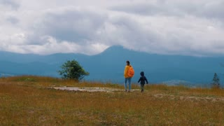 Mother with son hiking in scenic mountains