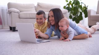 Mother with two kids using laptop on floor