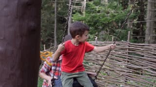 Mum helps the son swinging on the tire swing in slow motion
