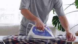 Muscular male hands ironing a shirt
