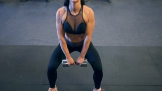 Muscular woman in black sportswear doing squat with dumbbell