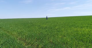 Old man in black glasses walking on green field
