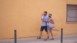 Parents walking with little baby along the street