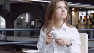 Pleased female drinking coffee while sitting in the cafe