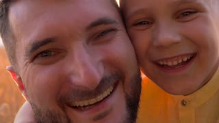 Positive father and son smiling at camera